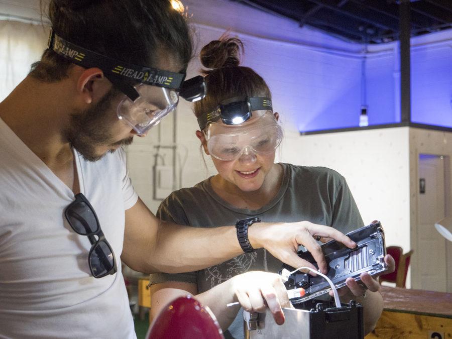 A couple takes apart a machine at CHAOS - photo by Dennis Spielma